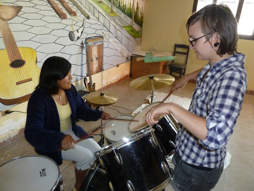 A Projects Abroad volunteer teaches a student to play the drums on the Music Project in Bolivia.
