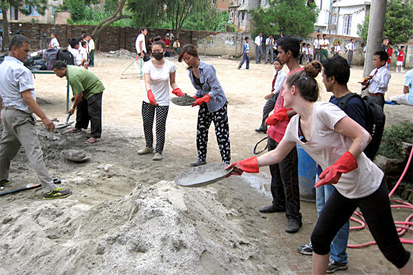 A group of Projects Abroad volunteers help put in a new floor at a school in Nepal