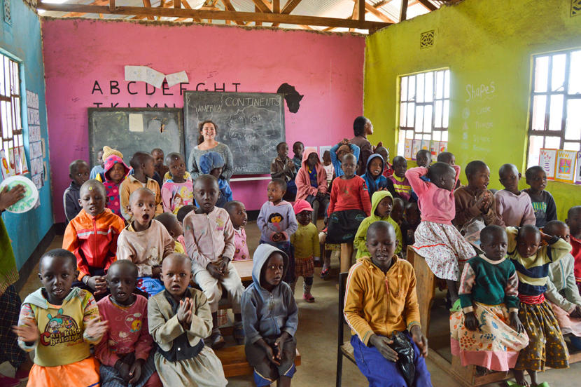 A Projects Abroad volunteer with a full classroom at an elementary school in Tanzania