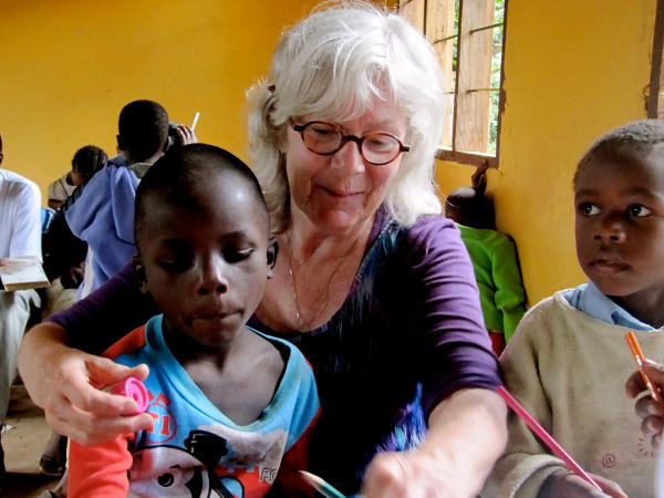 A Projects Abroad volunteer helps children with an educational activity at a Care project.