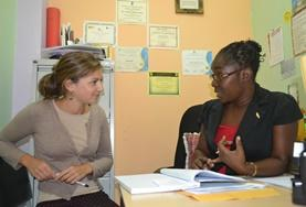 A volunteer discusses a patient with a psychologist in Jamaica.