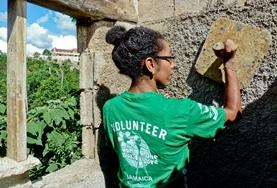 A volunteer plasters the wall of a new house built in Jamaica over Easter.
