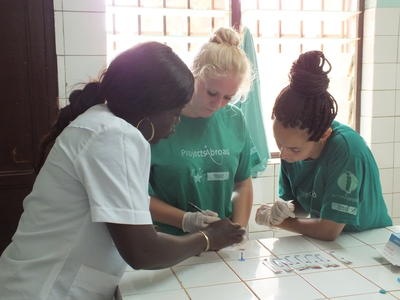 Pharmacy interns practice testing blood samples under supervision in Ghana.