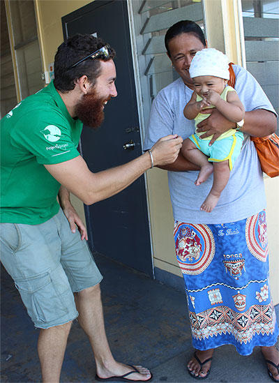 A nutrition volunteer laughs with a baby during a nutrition outreach in Fiji.