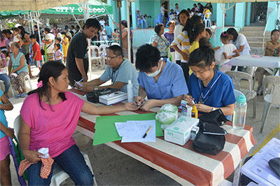 Projects Abroad Public Health volunteers talk to a local woman during a medical outreach in the Philippines.
