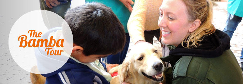 Female volunteer working with child and dog at the Canine Therapy Project in Bolivia.