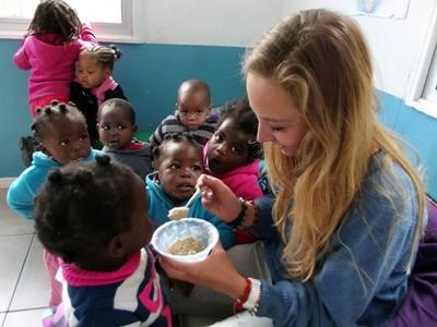 A Care volunteer feeds a child in South Africa during her project.