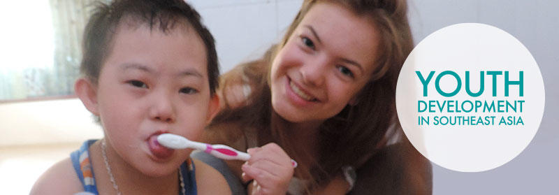 Projects Abroad Vietnam volunteer assists a local child with a toothbrush at a Care placement in Hanoi.