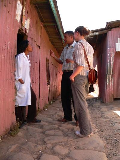 Journalism interns in Africa interview a local woman for an article.