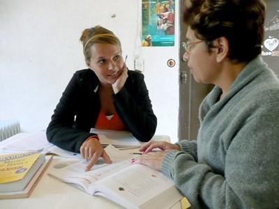 Volunteer on an International Development project in Asia reviews material with staff