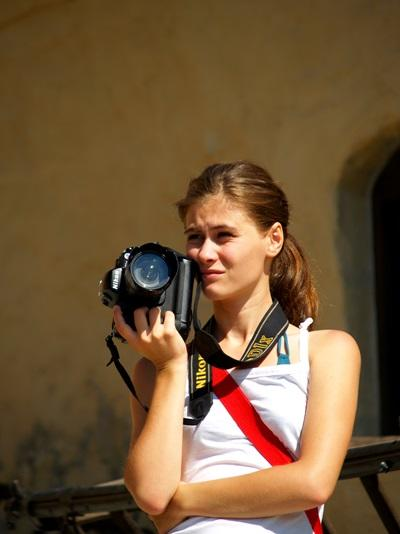 Journalism intern holding a camera on her project in Romania, Europe.