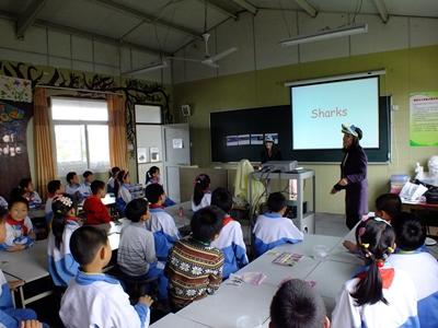 Chinese students listen to a volunteer talk about the importance of sharks.