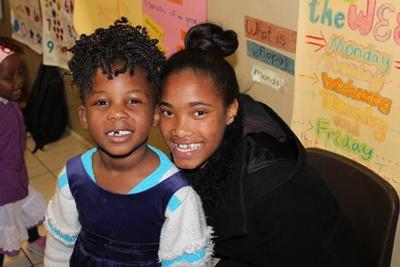 A local teacher with a young child at a South African kindergarten in Cape Town, Africa.