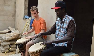 A local musician teaches a Projects Abroad volunteer to play the Djembe drum in Senegal, Africa