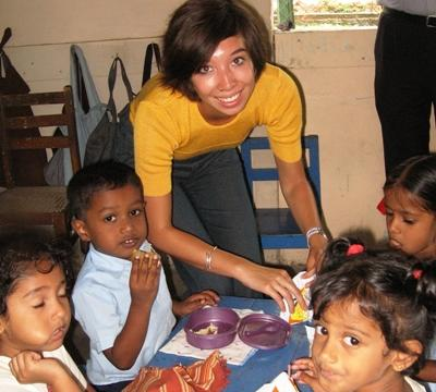 Volunteer feeding children at a care center on a Care Project in Asia