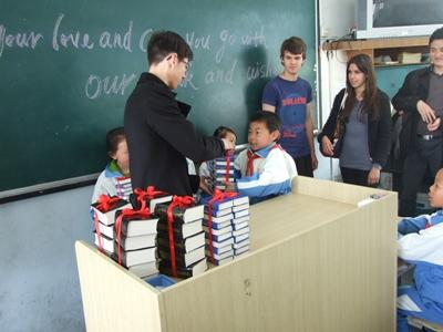 A Teaching volunteer distributes books to children at a school in Asia with Projects Abroad.