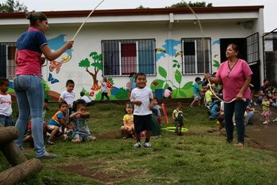 Volunteers and children playing jump rope outside of a Care project placement in Central America