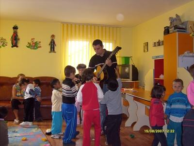 Volunteer playing the guitar for a class of children on a project in Europe.