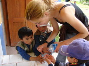 Volunteer washing children's' hands at a care center project in South America