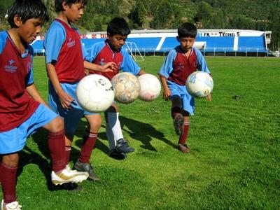 Students practice kicking soccer balls at a school on the Sports Project in South America