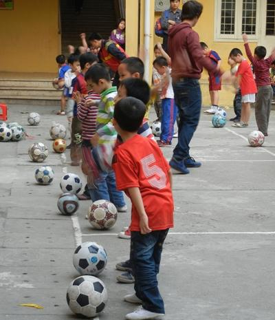 Children practicing soccer with their volunteer sports coach at a school in Southeast Asia