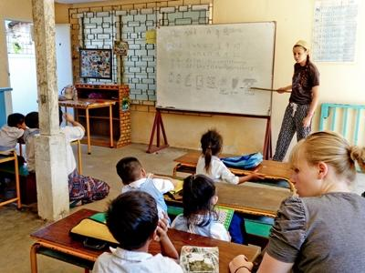 Volunteer teaching English vocabulary to a classroom of students in Southeast Asia
