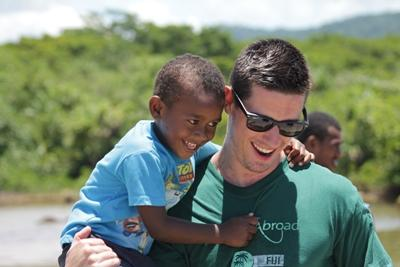 Volunteer playing with a young boy on the Care project in the South Pacific