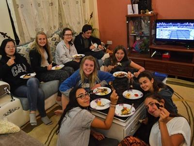 High School Special volunteers enjoy a Kenyan barbecue in the living room of their host family's home