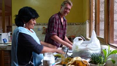 A host mother teaches a volunteer how to cook local Peruvian cuisine
