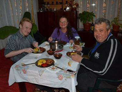 Volunteer eats a meal with his host family in Romania