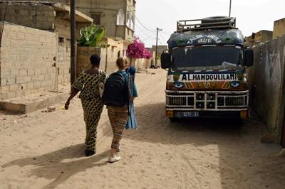 Projects Abroad volunteer and staff member walk down a street, past a bus, in Saint Louis, Senegal