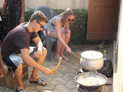 Projects Abroad volunteers participate in a traditional cooking lesson in Togo