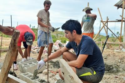 Volunteers on the Disaster Relief project in the Philippines help build a house.
