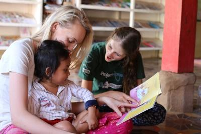 Projects Abroad Care & Community volunteers read aloud to Cambodian children