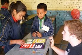 A 19+ Care & Community volunteer in Nepal helps children complete an activity at a day care centre.