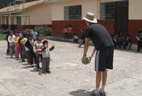 A 19+ Care & Community volunteer in Peru plays a ball game with young children.