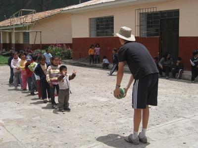 Projects Abroad volunteer plays with local children at a Care & Community placement in Peru