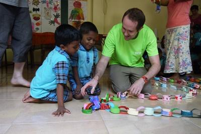 Projects Abroad Care & Community volunteer helps Sri Lankan children with an arts and crafts activity