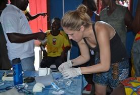 In Ghana, a volunteer on the 19+ Public Health Project assists staff at during a medical outreach.