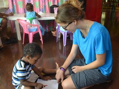 Projects Abroad volunteer helps a child with an educational activity at a care centre.