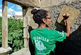 A Building volunteer plasters the wall of a house in Jamaica.
