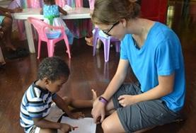 A child completes an activity with the assistance of a volunteer in Belize during her Alternative Spring Break.