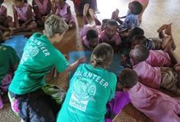 Volunteers help children with an activity in Fiji during their Alternative Spring Break.