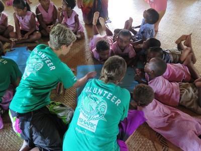 Kindergarten children work on a creative activity with the help of volunteers
