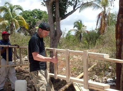 A Projects Abroad volunteer carries a ladder at the Building Project in Jamaica during his spring break.