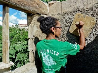 Volunteer helps to construct a building on the Alternative Spring Break Building project in Jamaica