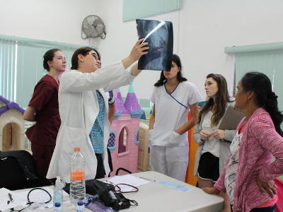 Group of Projects Abroad Public Health interns look at x-ray scans while listening to a Mexican doctor at an outreach in Guadalajara.