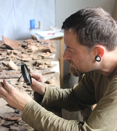 A Projects Abroad Archaeology staff member on the Inca Project uses a magnifying glass to take a close look at ceramics found in Huyro, Lucumayo Valley