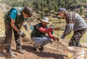 A group of volunteers examine an excavation site at the Archaeology Project in Peru.