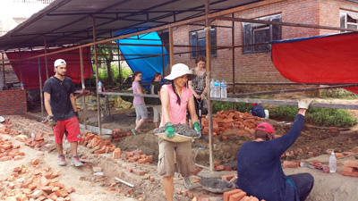 A group of volunteers assist with the construction of a new classroom in Nepal.